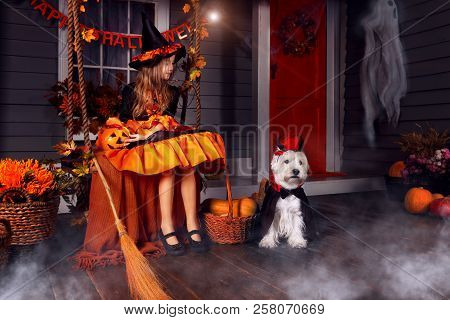 Funny Girl Child Kid In Halloween Orange Costume Playing Outdoor With Spooky Jack Pumpkins With Scar