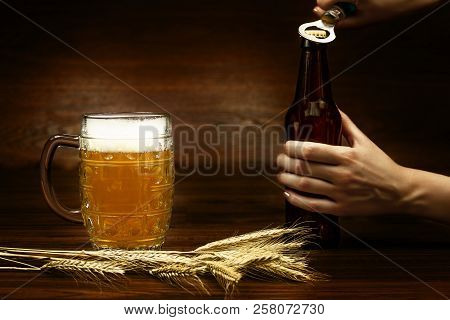 Hand with bottle of germany beer for october fest and mug pint glass cup of beer with piece of wheat on wooden background. Ready for october beer festival in autumn october month in germany. Beer day poster