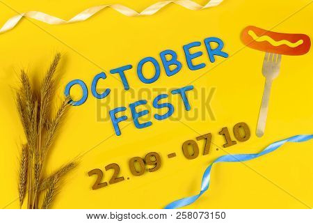 """Germany october fest concept. Wheat, fork with sausage with mustard and blue wooden text """"October fest 22.09 - 07.10"""" on yellow background.  Ads event of october beer festival in autumn october month poster"""