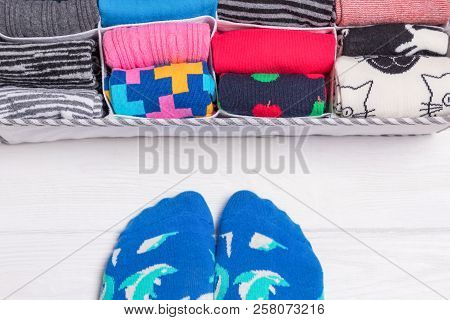 Box With Different Colorful Socks. Feet Selfie And A Socks Organizer On A White Background. Top View