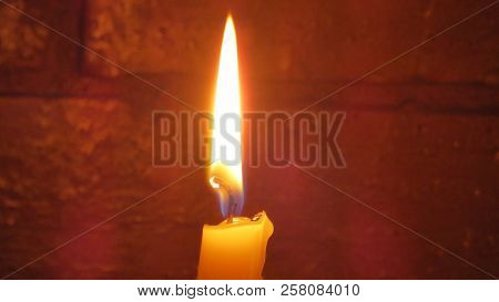Wax Chirch Candle Burning In Front Of Red Brick Wall
