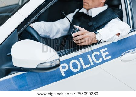 partial view of male police officer in bulletproof vest holding walkie-talkie in car poster