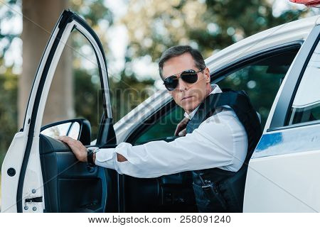 selective focus of mature policeman in bulletproof vest and sunglasses walking out from car poster