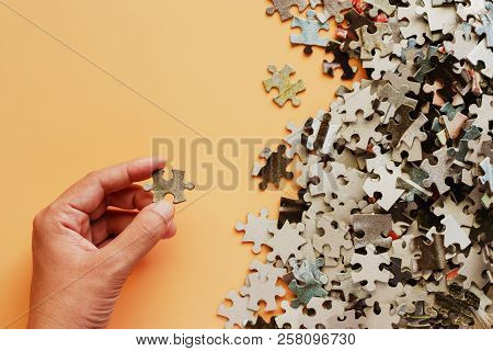 Hand Holding Piece Of Jigsaw Puzzle On Beige Color Background For Thinking And Problem Solving Conce