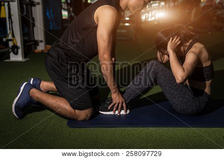 Fitness, Sport, Training, Gym And Lifestyle Concept - Woman With Personal Trainer Doing Sit Ups In G