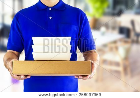 Food Delivery Service Or Order Food Online. Delivery Man In Blue Uniform With Hand Holding Food Pack