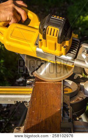 Tradesman Using Electric Circular Store To Cut Wood