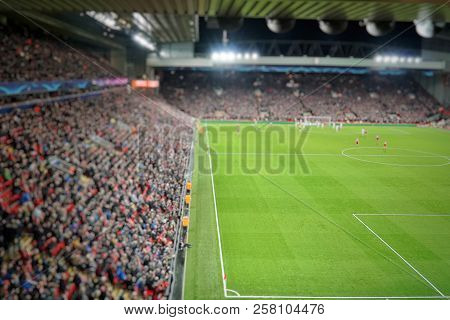 Blurred Background Of Football Players Playing And Soccer Fans In Match Day On Beautiful Green Field