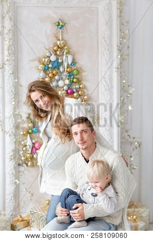 Happy Family Having Fun At Home. Christmas Morning In Bright Living Room. Young Parents With Little