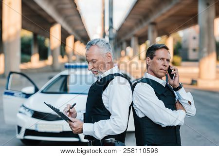Mature Police Officer Talking On Smartphone And Standing With Colleague Back To Back While He Writin