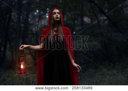 Elegant Mystic Girl In Red Cloak With Kerosene Lamp Walking In Dark Woods