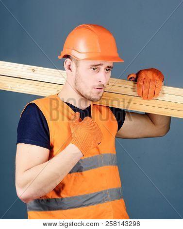 Carpenter, Woodworker, Strong Builder On Serious Face Carries Wooden Beam On Shoulder. Wooden Materi