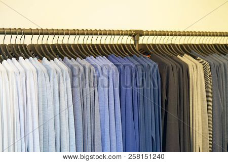 Clothes Hanger With T Shirt. Fashionable Clothing On Hangers In Shop. Sport Of T Shirts Are Hanging