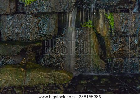 Closeup Of Small Waterfall Cascading Down Stone Wall Of Man Made Stream.