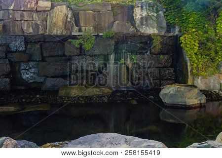 Wide Angle Of Man Made Stream With Waterfall Cascading Out Of Wall Of Large Stones.