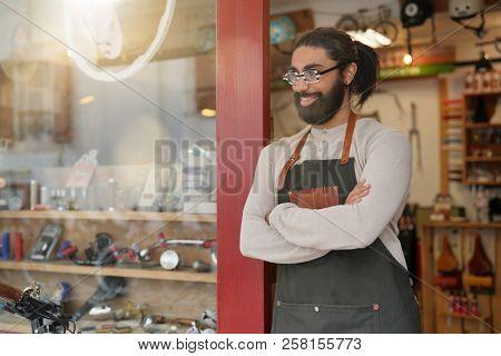Portrait of cycle repair shop owner standing by front door