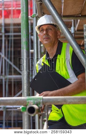 Male builder foreman, construction worker or site manager holding a clipboard, wearing a white hard hat and hi vis vest