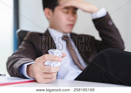 Unhappy Young Businessman Hand Holding A Crumpled Paper And Another Squeezing Head With Hand. Negati