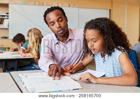 Teacher working with elementary school girl at her desk
