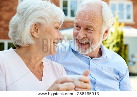 Retired Couple Sitting On Bench With Hot Drink In Assisted Living Facility poster