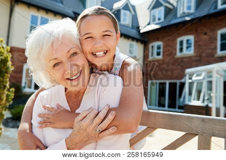 Portrait Of Granddaughter Hugging Grandmother On Bench During Visit To Retirement Home poster