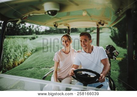 Happy Young Couple In White Cart On Golf Field. Young Family. Golf Club. Sports In Summer. Vehicle O