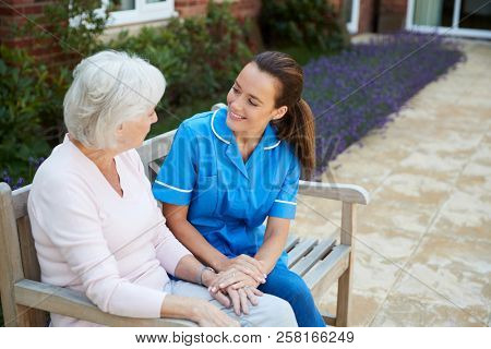 Senior Woman Sitting On Bench And Talking With Nurse In Retirement Home