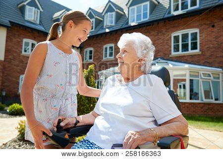 Granddaughter Visiting Grandmother Sitting In Motorized Wheelchair In Retirement Home poster