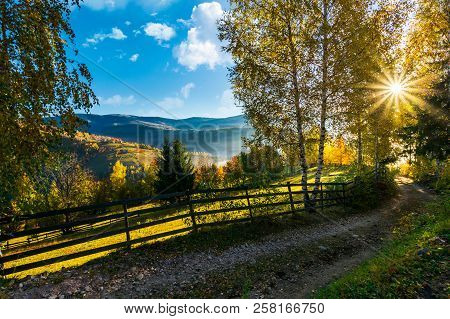 Country Road Down The Hill In To The Sunrise. Beautiful Rural Landscape In Autumn. Wooden Fence Alon