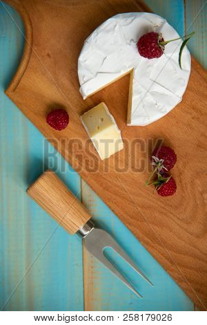 Cheese Camembert With Raspberries On A Blue Background