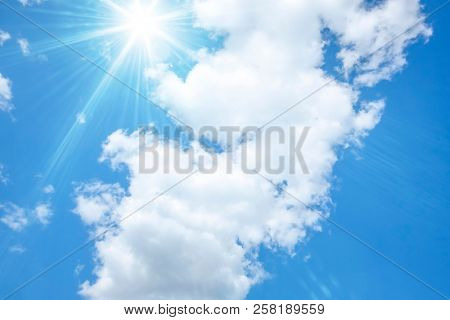 An image of a blue sky with bright sun and white clouds