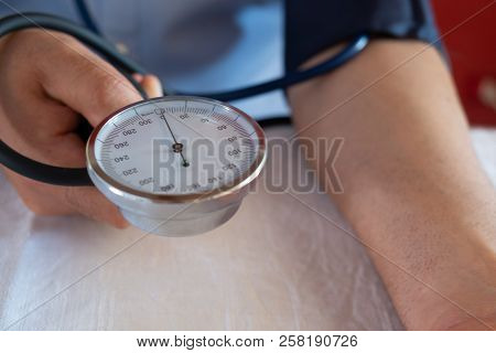Hypertensive Patient Performing A Blood Pressure Auto Test / Man Self-monitoring Of Blood Pressure W