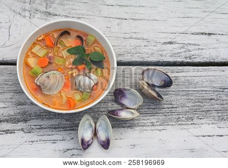 Bowl With Manhattan Clam Chowder On Weathered Wood Background.