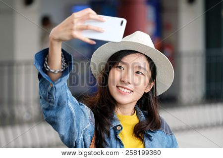 Young Cute Asian Woman In Casual Style Making Selfie With Her Smartphone In The Urban City Outdoors