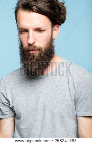 Sad Depressed Frustrated Dull Bearded Man. Portrait Of A Disappointed Sullen Hipster Guy On Blue Bac