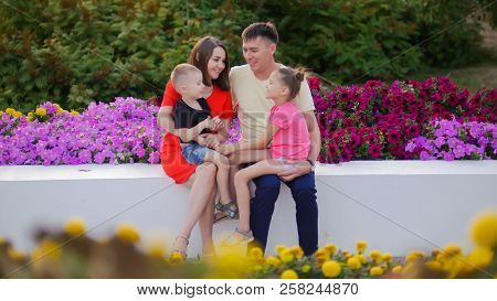 Young Happy Family In The Park Among The Flowers. The Little Son Sits On His Mother's Lap, The Daugh