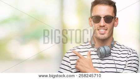 Handsome young man wearing headphones cheerful with a smile of face pointing with hand and finger up to the side with happy and natural expression on face looking at the camera.