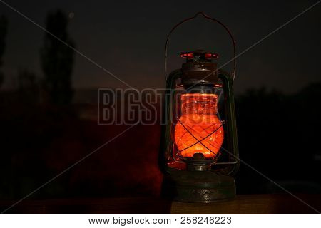 Horror Halloween Concept. Burning Old Oil Lamp In Forest At Night. Night Scenery Of A Nightmare Scen