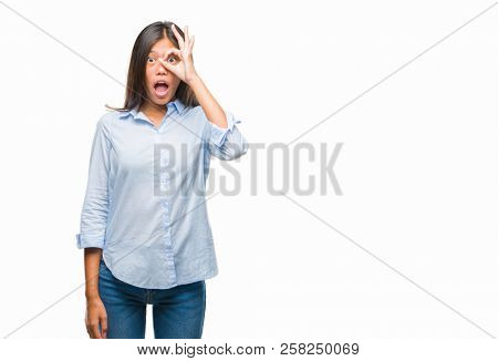 Young asian business woman over isolated background doing ok gesture shocked with surprised face, eye looking through fingers. Unbelieving expression.