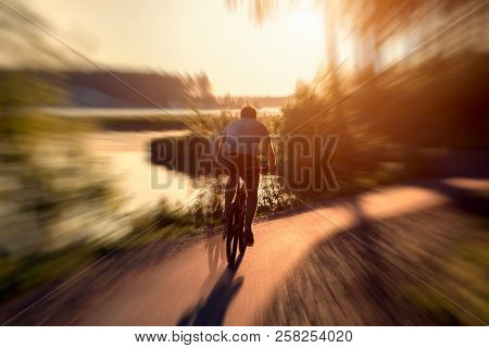 A Cyclist Rides A Bike Along A Bicycle Path. Cyclist In Motion Against The Backdrop Of The Setting S