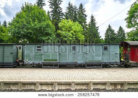 Train Wagon With Cargo On A Railway At A Station With Green Trees In The Background In Cloudy Weathe