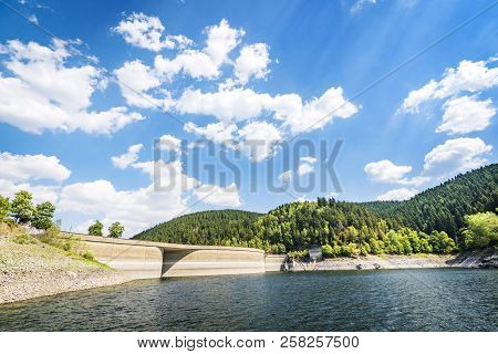Lake Landscape With A Dam In Summer With A Forest In The Background