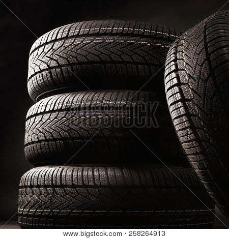 Closeup Of Four Tires Against A Black Background