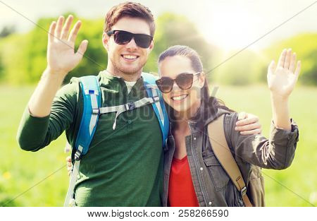 travel, hiking, backpacking, tourism and people concept - happy couple with backpacks waving hands outdoors