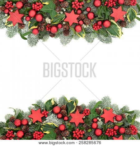 Christmas Festive background border with red bauble decorations, winter flora of holly berries, snow covered spruce pine, ivy, pine cones and mistletoe on white background with copy space.