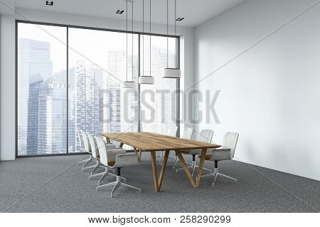 Side View Of Modern Office Conference Room With Panoramic Windows, A Gray Carpet And A Long Wooden T
