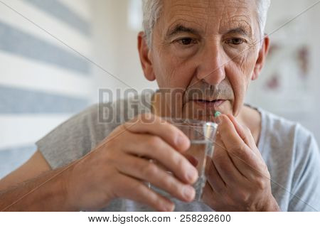 Ill senior man taking medicine for hypertension. Portrait of elderly man taking pills for depression. Old man swallowing pill with glass of water.
