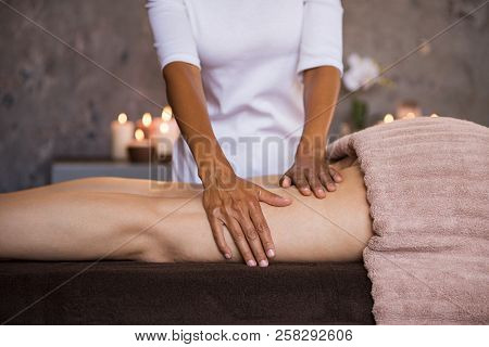 Therapeutic massage for senior woman by beautician at spa. Closeup of professional masseuse hands massaging woman legs at wellness center. Anti cellulite treatment and leg drainage on mature woman.