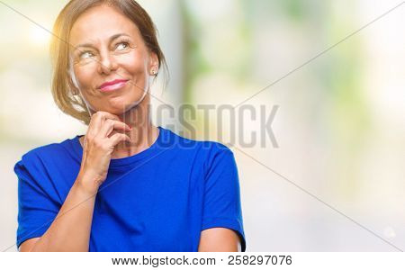 Middle age senior hispanic woman over isolated background with hand on chin thinking about question, pensive expression. Smiling with thoughtful face. Doubt concept.