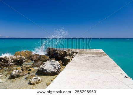 Clear Sky, Turquoise Blue Sea, Rocks And Concrete Pier, With Splashing Waves In Greece.